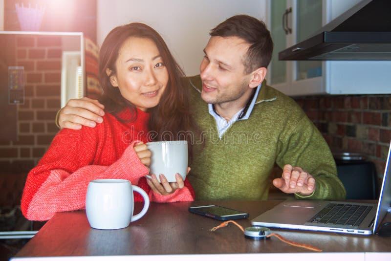 Unga intressanta par som hemma ser en bärbar dator i köket och rymmer en smartphone Ett internationellt par på det inter- fotografering för bildbyråer