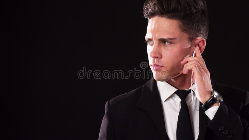 Unga James Bond i en dräkt lyssnar till faktumet som i hans speciala skalm arkivbilder