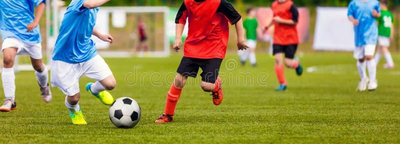 Unga Junior Football Match Spelare som kör och sparkar Footbal royaltyfria foton