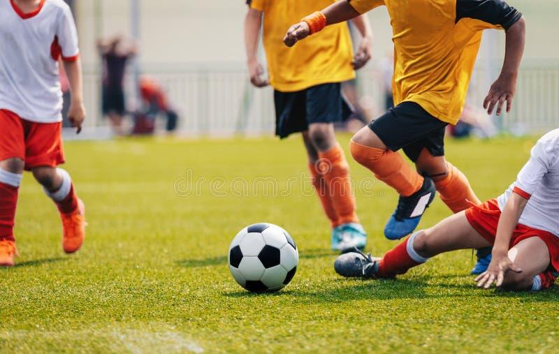 Unga Junior Football Match Spelare som kör och sparkar fotbollbollen fotografering för bildbyråer
