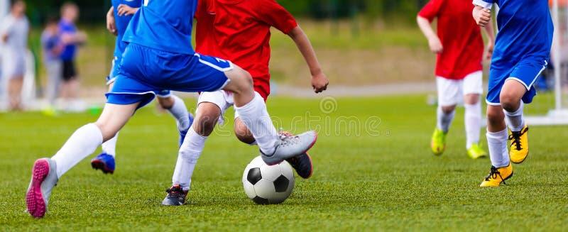 Unga Junior Football Match Spelare som kör och sparkar fotbollbollen arkivbilder