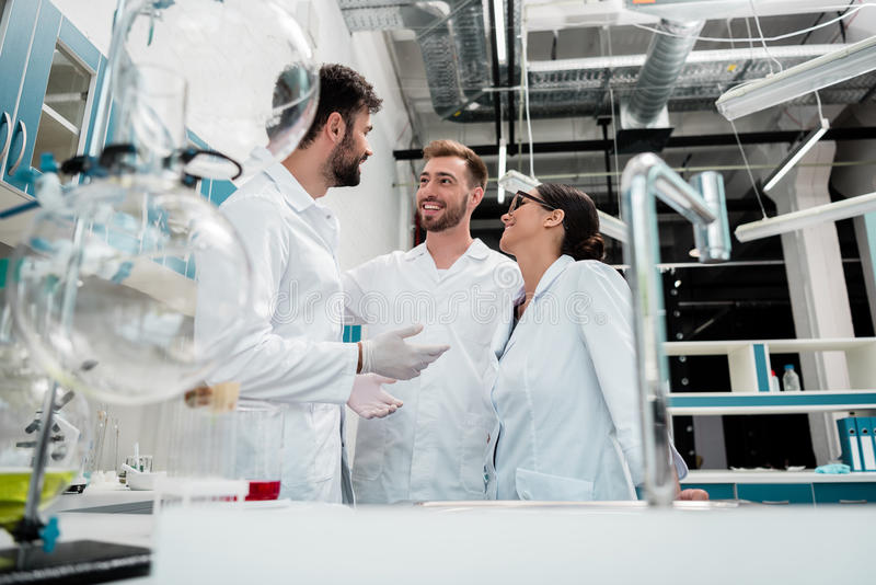 Unga kemister i vita lag som står och talar i laboratorium arkivfoto