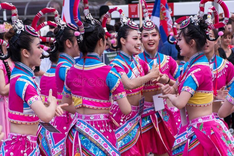 Unga kinesiska flickor dansar folkdans i traditionella dräkter arkivbilder