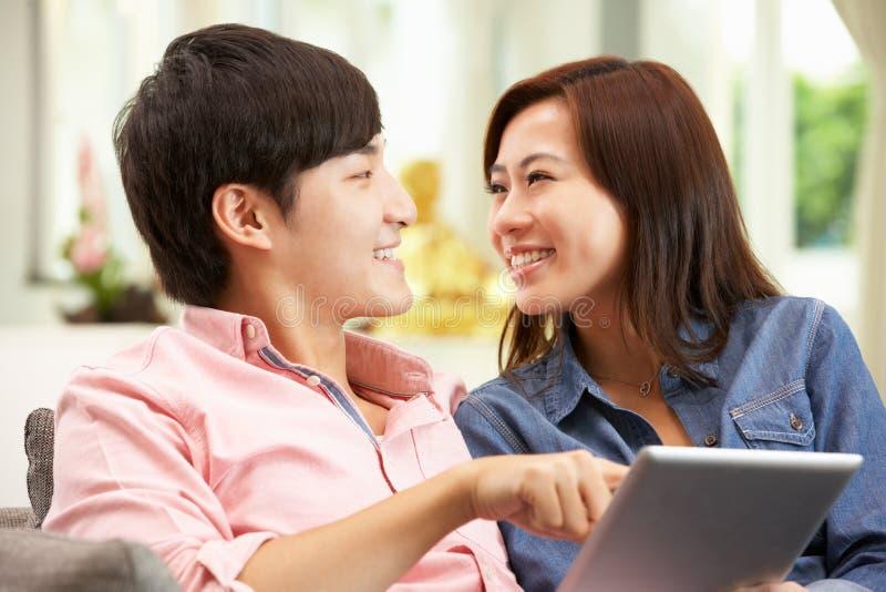 Unga kinesiska par genom att använda den Digital tableten royaltyfria bilder
