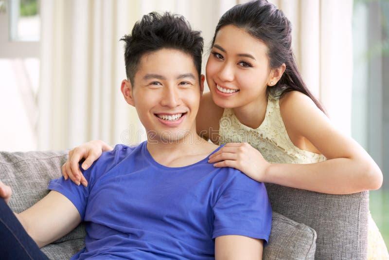 Unga kinesiska par som hemma kopplar av på sofaen arkivfoton