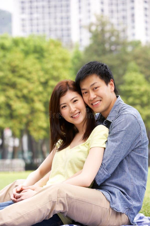 Unga kinesiska par som tillsammans kopplar av i Park arkivbild