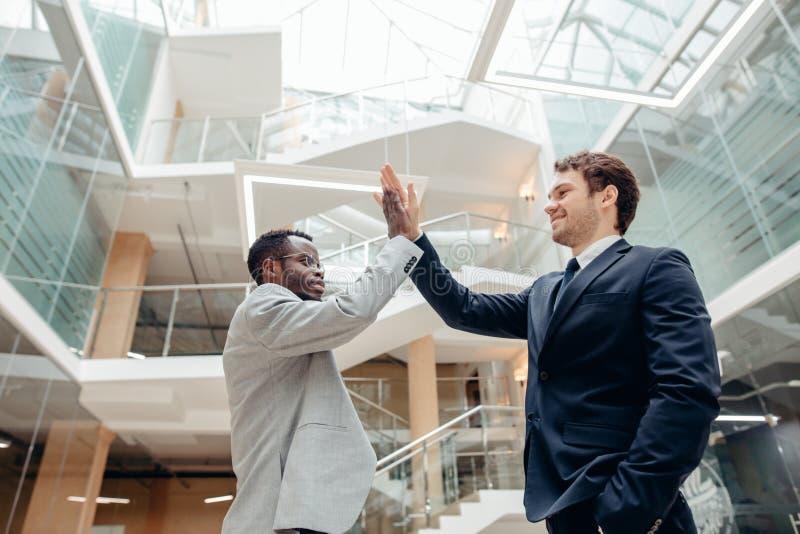 Unga kollegor som ger sig höjdpunkt fem, medan stå i ett kontor arkivbild