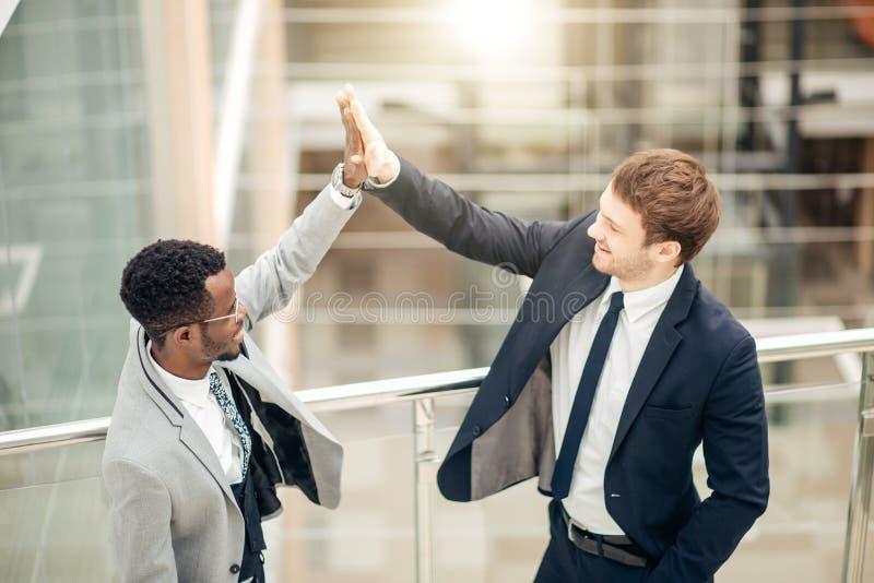 Unga kollegor som ger sig höjdpunkt fem, medan stå i ett kontor arkivfoton