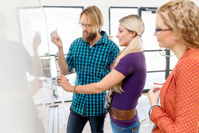 Unga kontorsarbetare som diskuterar arkivfoton