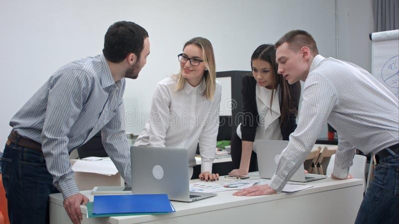 Unga kontorscoworkers som har ett upptaget möte royaltyfria foton