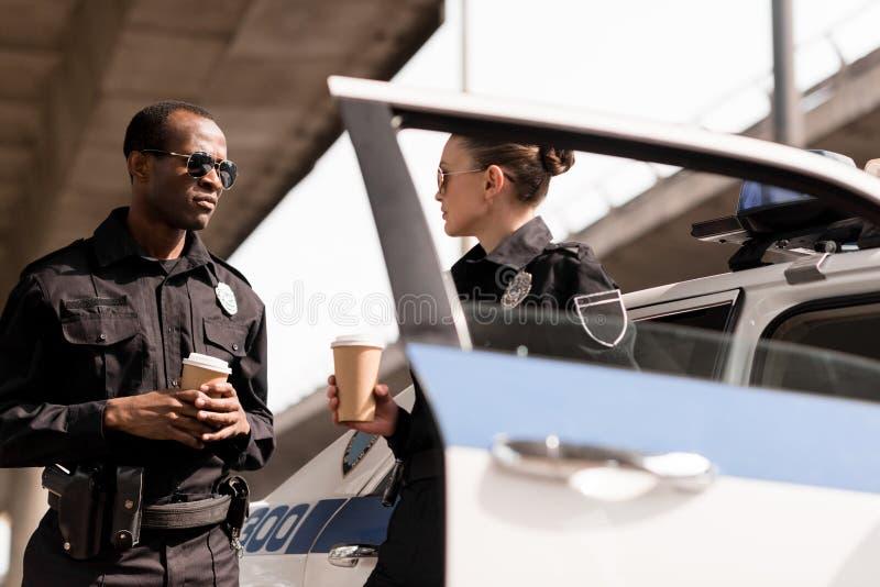unga koppla av poliser som dricker kaffe royaltyfri fotografi