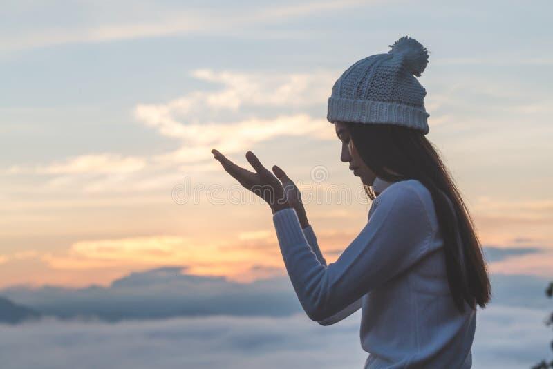 Unga kristna öppna kvinnahänder gömma i handflatan upp dyrkan och att be till guden på soluppgång, Christian Religion begreppsbak royaltyfria foton