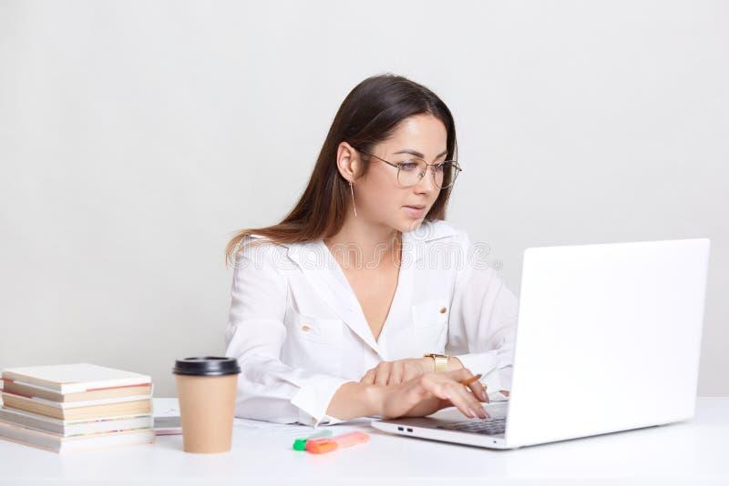 Unga kvinnliga administrativa arbeten på bärbar datordatoren, söker information i internet, den iklädda vita varma drycken för dr arkivfoto