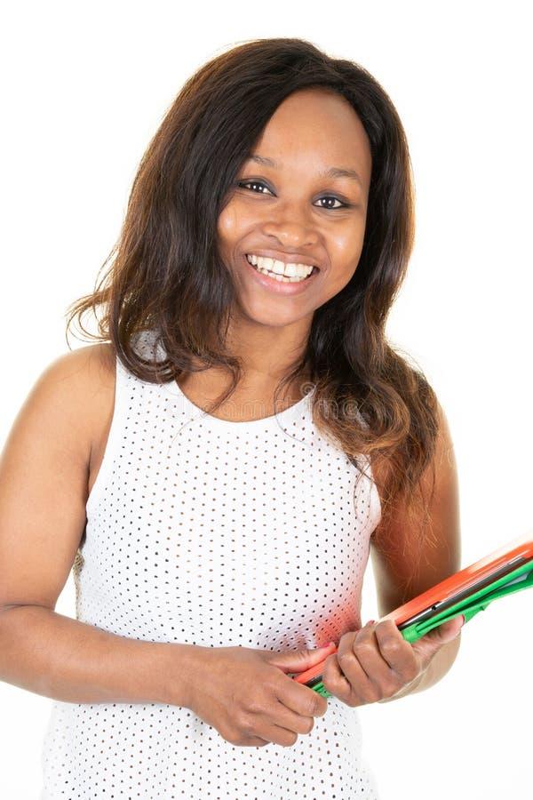 Unga kvinnliga böcker för minnestavla för afrikansk amerikanhögskolestudentinnehav som isoleras på vit royaltyfri bild