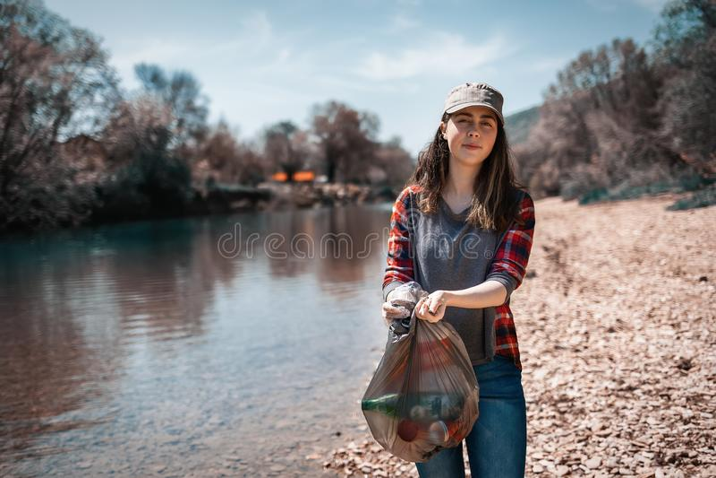 Unga kvinnliga band för en volontär en påse av avskräde som står vid floden Begreppet av jorddagen och ekologi och miljö- arkivfoton
