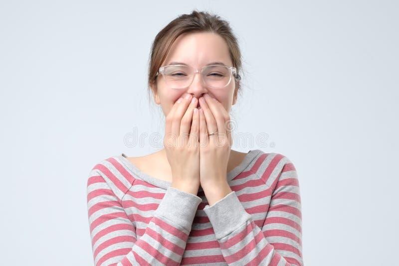 Unga kvinnliga fniss joyfully, täcker munnen, som försök stoppar att skratta arkivbilder