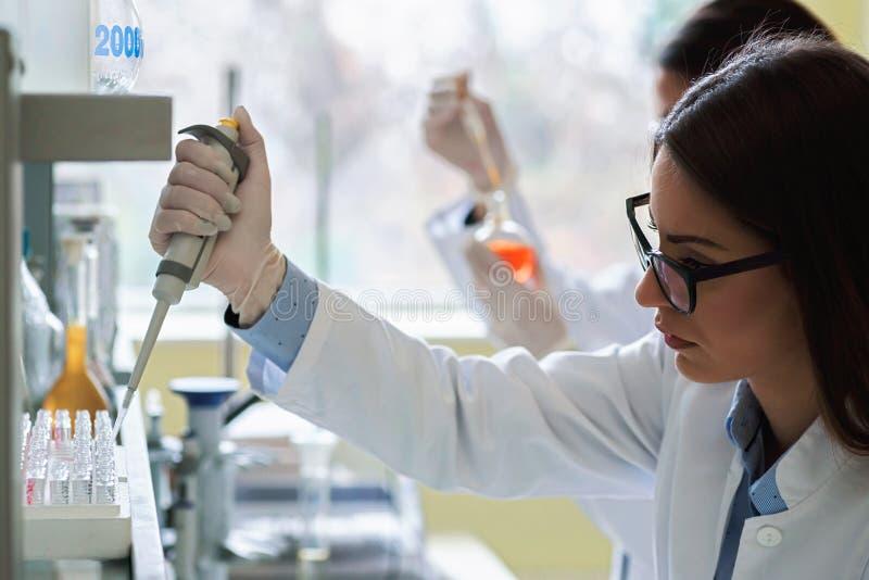 Unga kvinnliga forskare som för laboratoriumprovet arkivfoton