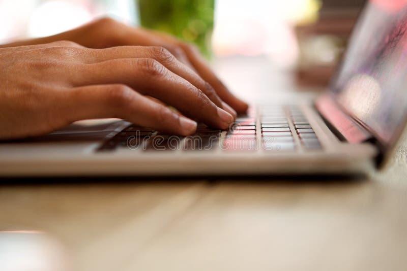Unga kvinnliga händer som arbetar på bärbar datordatoren royaltyfri fotografi
