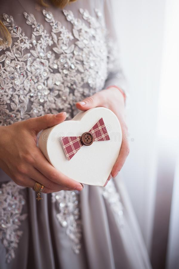Unga kvinnliga händer som rymmer gåvaasken i form av hjärta nära fönster i dagsljus royaltyfri foto