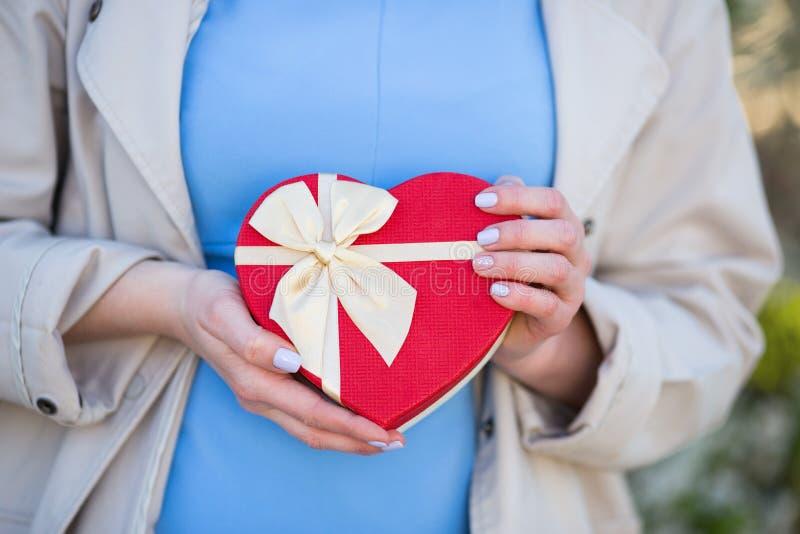 Unga kvinnliga händer som rymmer gåvaasken i form av röd hjärta med pilbågen arkivbilder