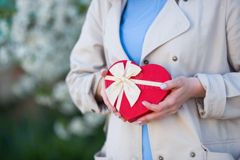 Unga kvinnliga händer som rymmer gåvaasken i form av röd hjärta med suddig vårbakgrund royaltyfria bilder