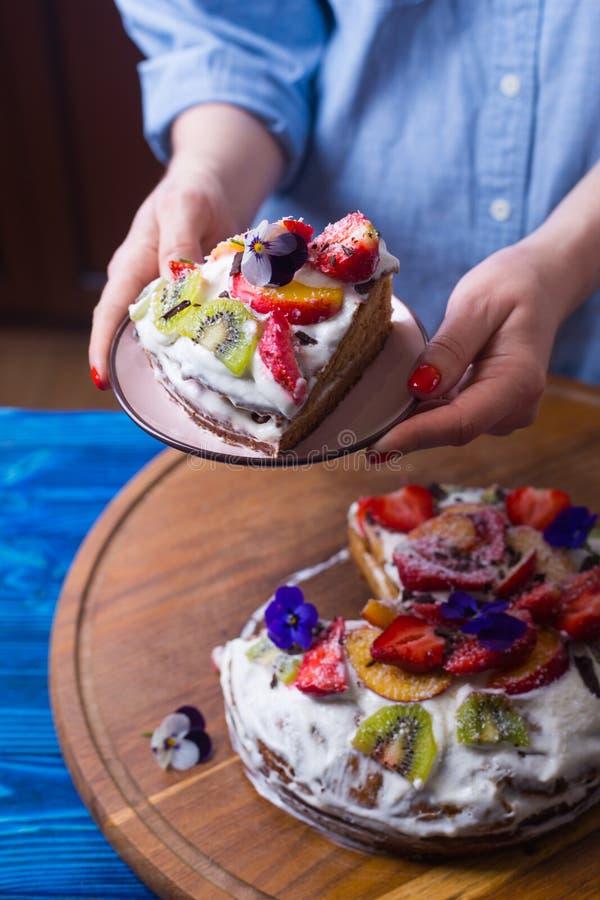 Unga kvinnliga händer som rymmer plattan med stycket av gräddfilkakan med frukter som dekoreras med blommor arkivbilder