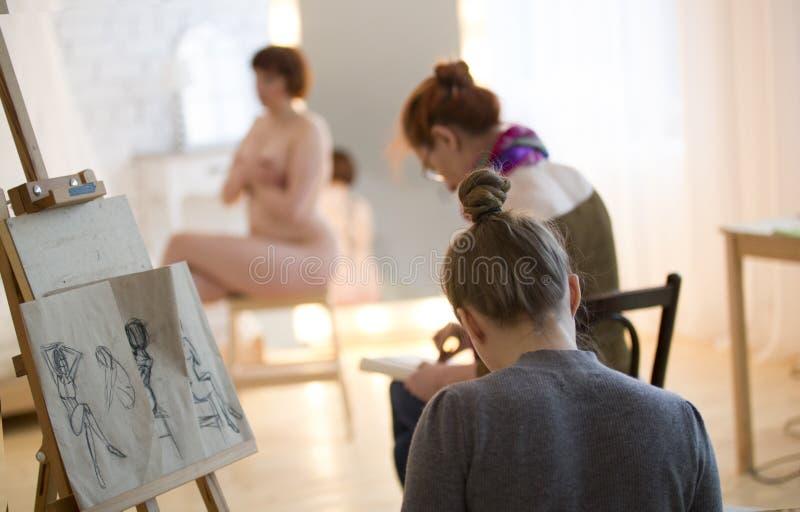 Unga kvinnliga konstnärer som skissar en näck modell i teckningsgrupp fotografering för bildbyråer