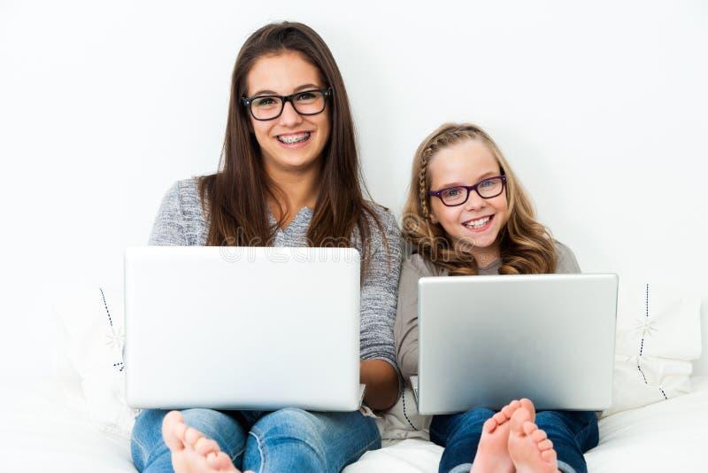 Unga kvinnliga studenter som kopplar av med bärbara datorer arkivbild