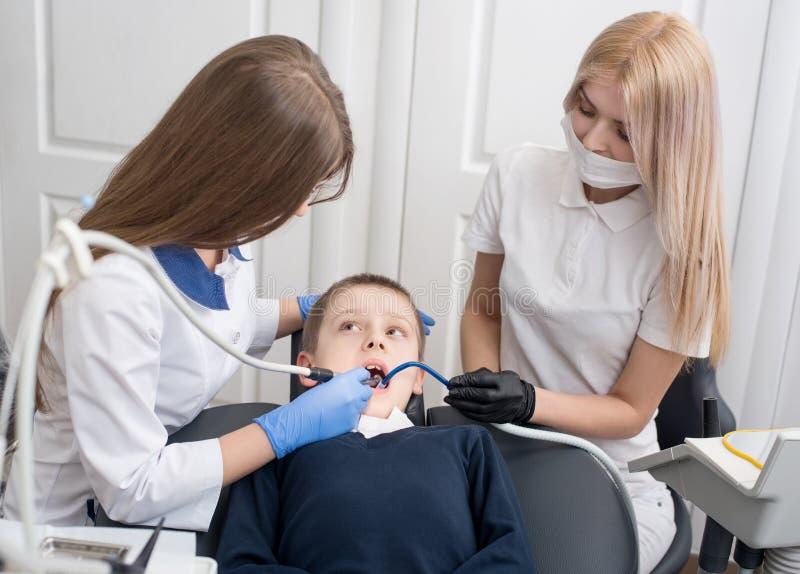 Unga kvinnliga tandläkare som undersöker och arbetar på pojkepatient arkivbilder