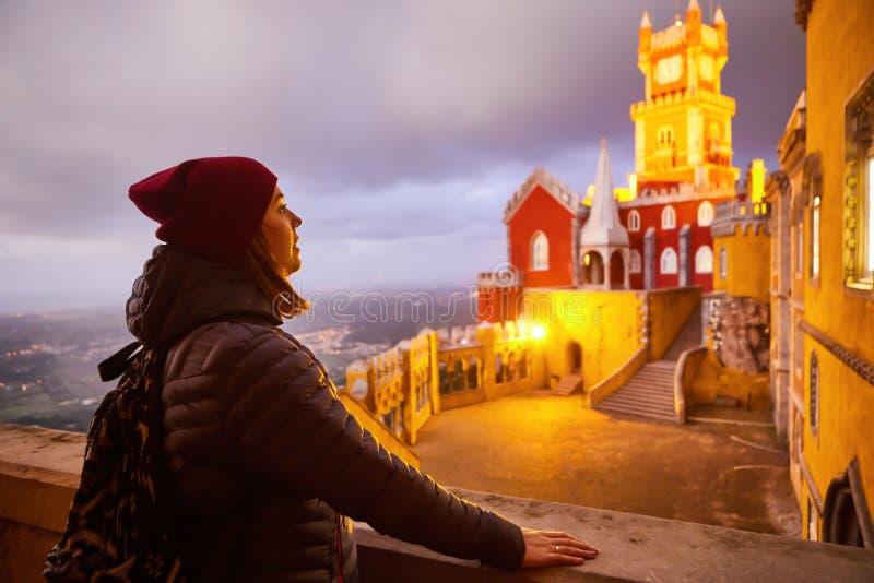 Unga kvinnliga turister går i Pena Palace, Sintra, Portugal på natten Resor och turism i Europa royaltyfri fotografi