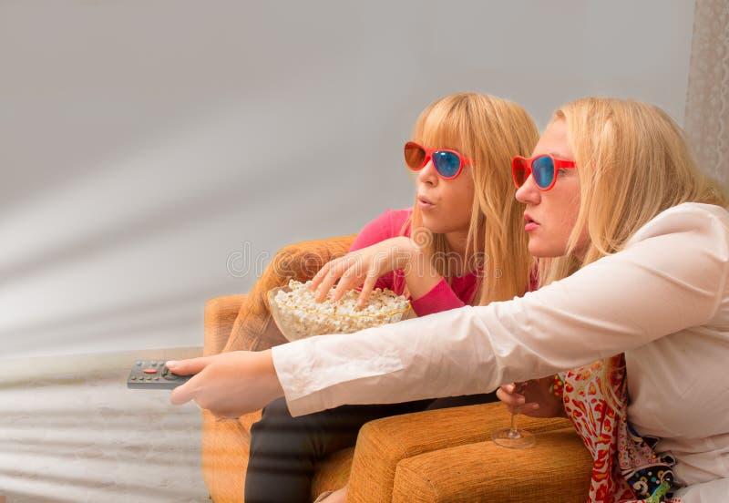 Unga kvinnliga vänner som håller ögonen på en film 3d se upphetsad royaltyfria foton
