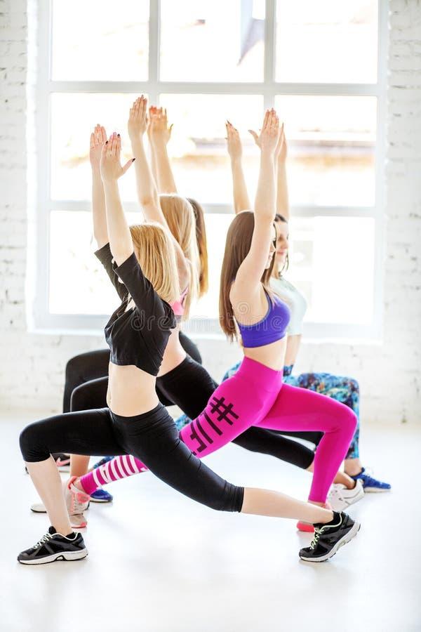 Unga kvinnor är på Pilates i idrottshall Begreppet av sportar, dans, arkivbild