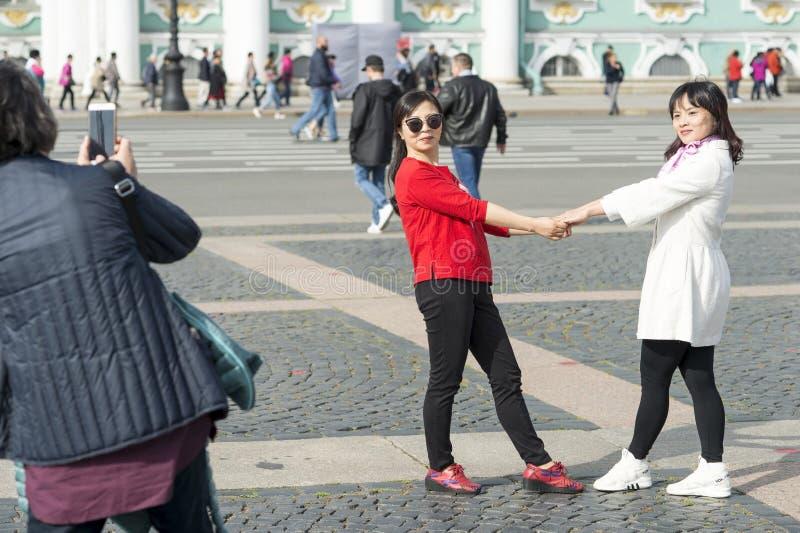 Unga kvinnor av det asiatiska utseendet fotograferas på slottfyrkant mot bakgrunden av eremitboningen i St Petersburg, arkivbilder