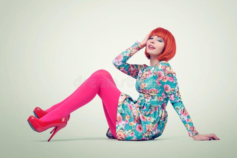 Unga kvinnor för glamorös rödhårig man som sitter på golvet relax arkivbild