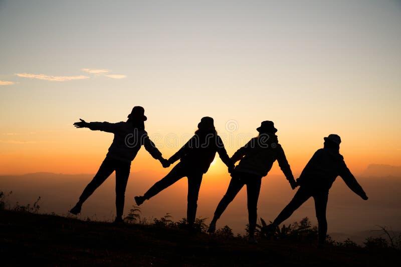 Unga kvinnor för soluppgångkontur som går handen - i - hand royaltyfria bilder