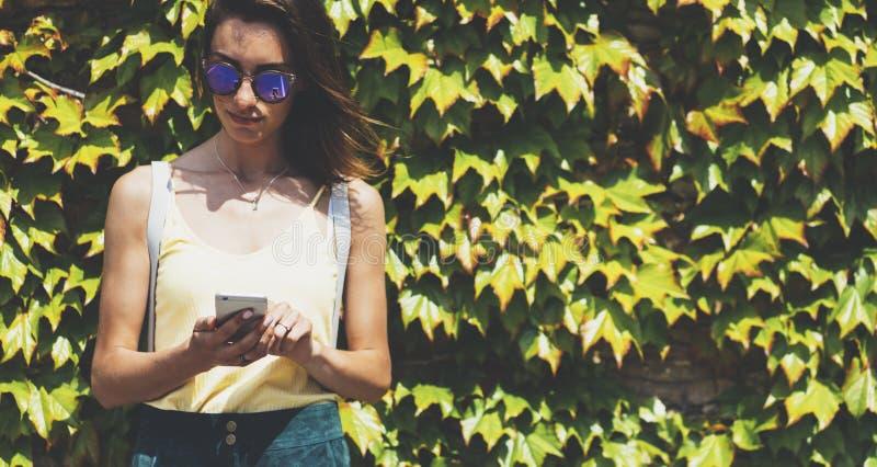 Unga kvinnor för stående i solglasögon genom att använda upp den smarta telefonen på för naturvägg för bakgrund grön åtlöje, kvin arkivbilder