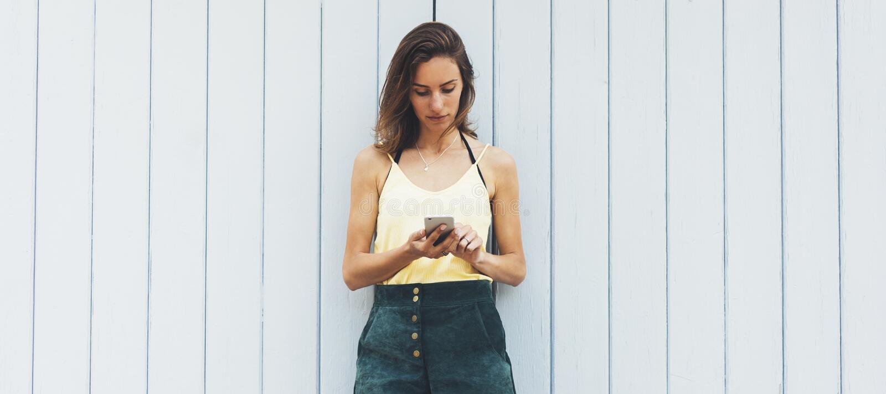 Unga kvinnor för stående som använder den smarta telefonen som isoleras på falsk bakgrund för vägg bakgrundstappningför träbräden royaltyfria bilder
