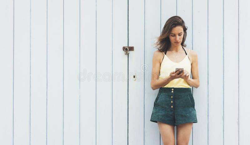 Unga kvinnor f?r st?ende som anv?nder den smarta telefonen som isoleras p? falsk bakgrund f?r v?gg bakgrundstappningf?r tr?br?den royaltyfri fotografi