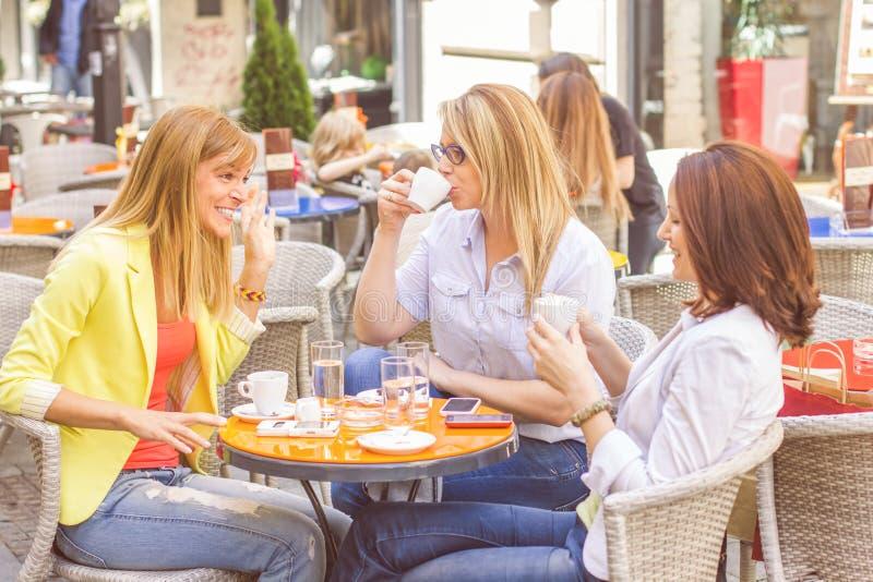 Unga kvinnor har kaffeavbrottet tillsammans royaltyfri fotografi