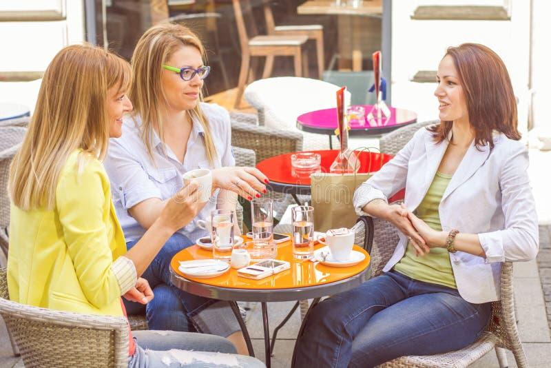Unga kvinnor har kaffeavbrottet tillsammans royaltyfria bilder