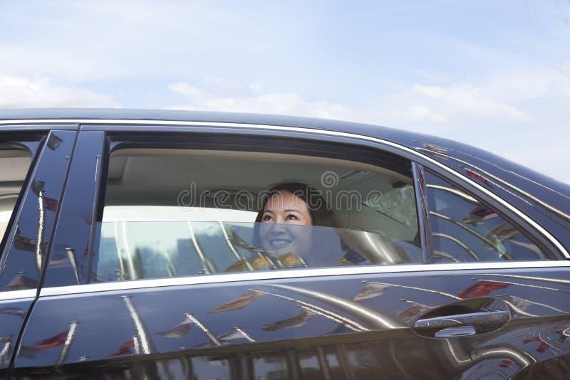 Unga kvinnor i baksätet av bilen som ser ut ur fönster. arkivfoto
