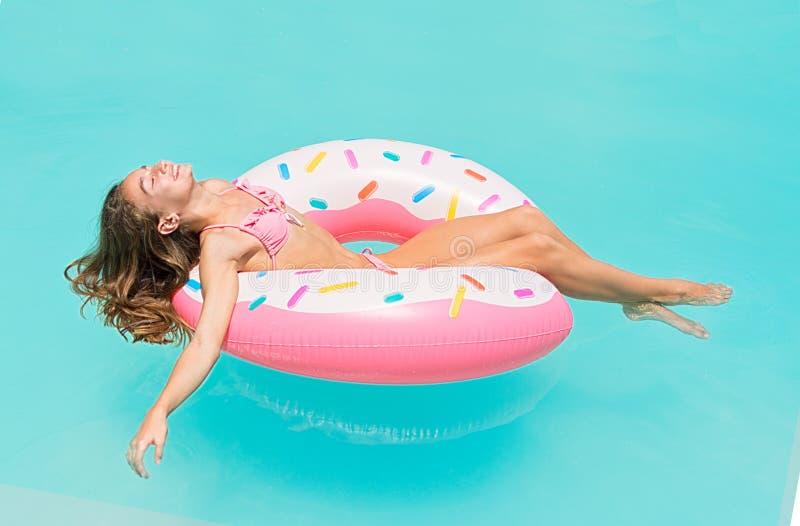 Unga kvinnor i bikinin som ner ligger på en uppblåsbar munk i simbassäng Flickan tycker om att solbada på att sväva uppblåsbar le royaltyfri bild