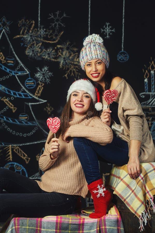 Unga kvinnor i jultomtenhattar för jul, arkivfoton
