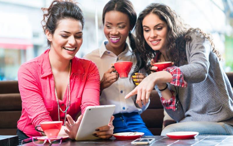 Unga kvinnor i kafét som tar selfie arkivbild