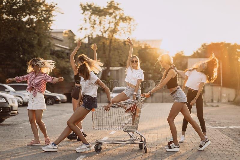 Unga kvinnor med en supermarketvagn har gyckel royaltyfria foton