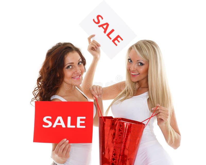 Unga kvinnor med försäljningstecknet. fotografering för bildbyråer