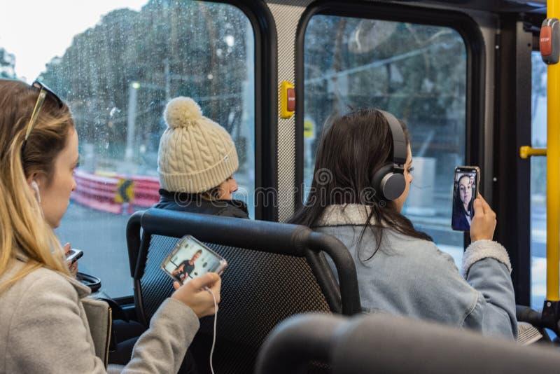 Unga kvinnor meddelar med deras mobila enheter på bussen royaltyfri fotografi