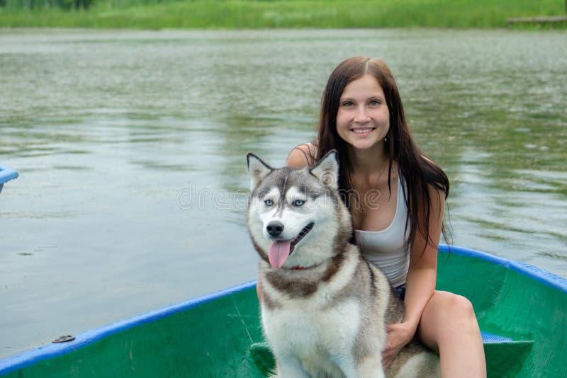 Unga kvinnor och hennes skrovliga vila för hund nära sjön i sommar arkivfoton