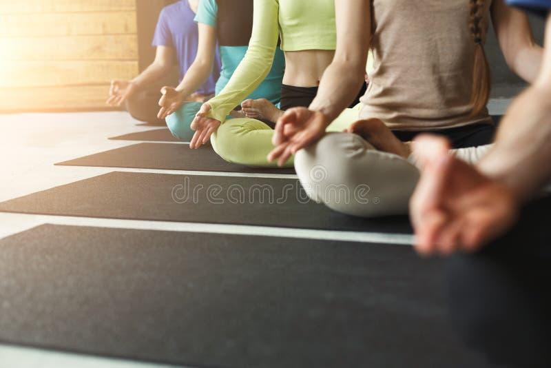 Unga kvinnor och män i yoga klassificerar, kopplar av meditation poserar