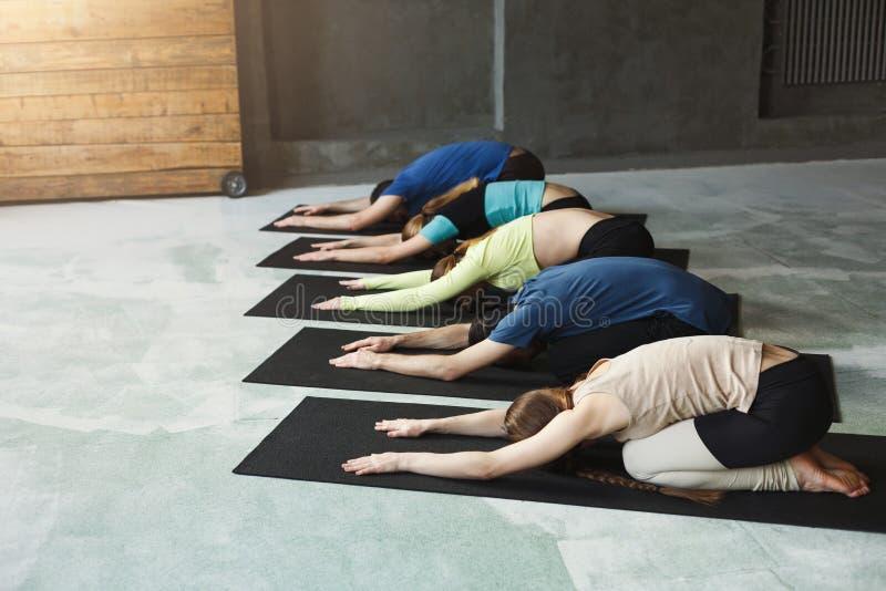 Unga kvinnor och män i yoga klassificerar, kopplar av meditation poserar fotografering för bildbyråer